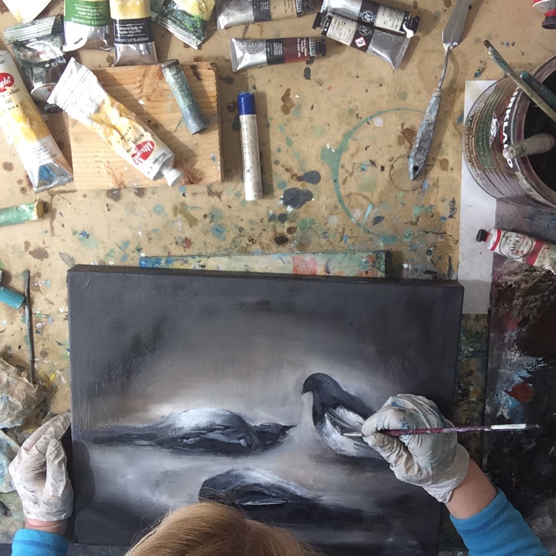 Fine artists Sara Richardson at work in the studio on a new small birds oil painting